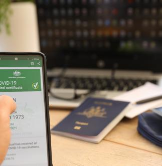 A person sits at their desk in front of their laptop and Australian passport, holding a phone which shows their COVID-19 digital certificate.